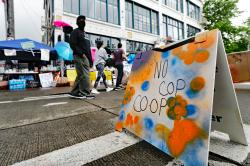 """People walk near what is being called the """"No Cop Co-op"""" were protesters and others can get free food and other supplies, Thursday, June 11, 2020, inside what is being called the """"Capitol Hill Autonomous Zone"""" in Seattle"""