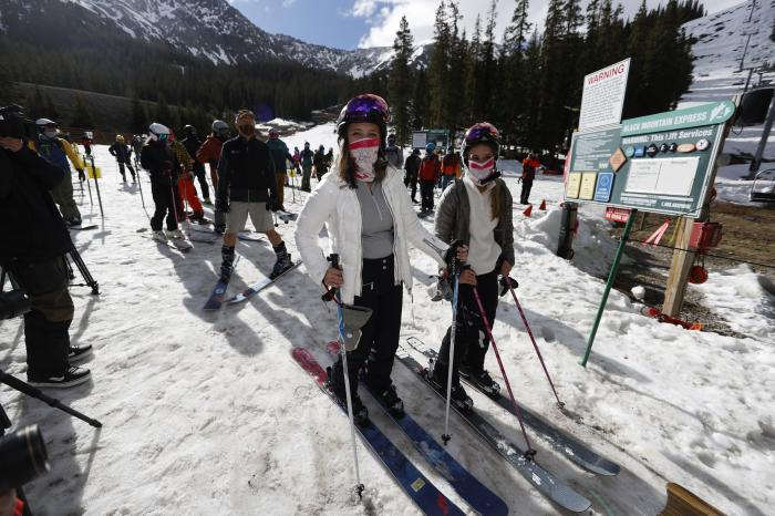 In this May 27, 2020, file photo, skiers wear face coverings as they wait to board a lift at the reopening of Arapahoe Basin Ski Resort,