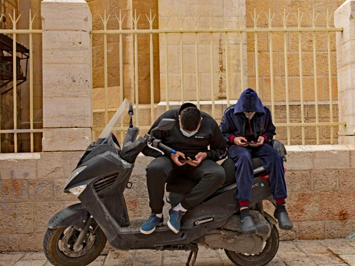 Young men scroll on their smart phones in the Old City of Jerusalem, Wednesday, Dec. 23, 2020