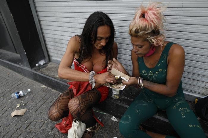 Honduran sex workers Carolina and Angora, split a small meal, as they wait for clients outside the Revolution subway station in Mexico City.