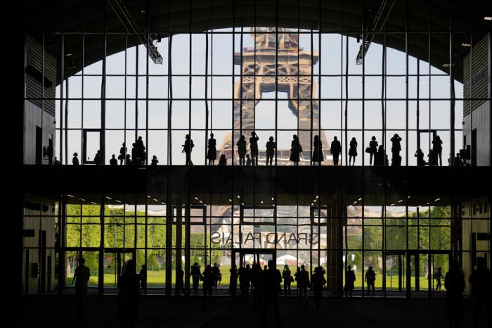 """Visitors gather during a presentation visit of the """"Grand Palais Ephemere"""", with the Eiffel Tower in the background, in Paris."""