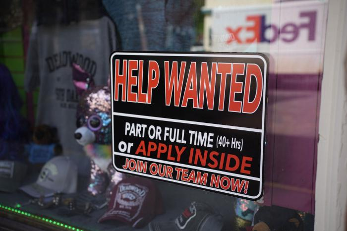 In this May 26, 2021 photo, a sign for workers hangs in the window of a shop along Main Street in Deadwood, S.D.