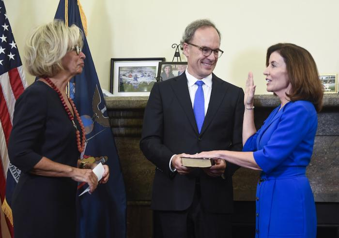 New York Chief Judge Janet DiFiore, left, swears in Kathy Hochul, right, as the first woman to be New York's governor while her husband Bill Hochul holds a bible during a swearing-in ceremony in the Red Room at the state Capitol, in Albany.