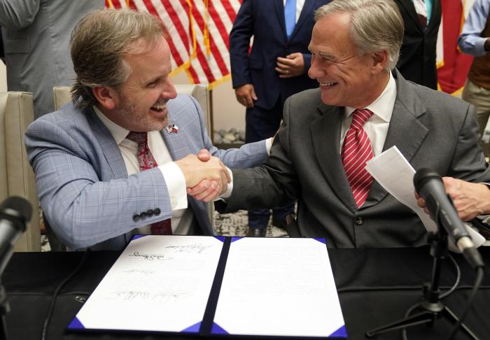 Texas Gov Greg Abbott and State Sen. Bryan Hughes, R-Mineola, shake hands after Abbott signed Senate Bill 1, also known as the election integrity bill, into law in Tyler, Texas.