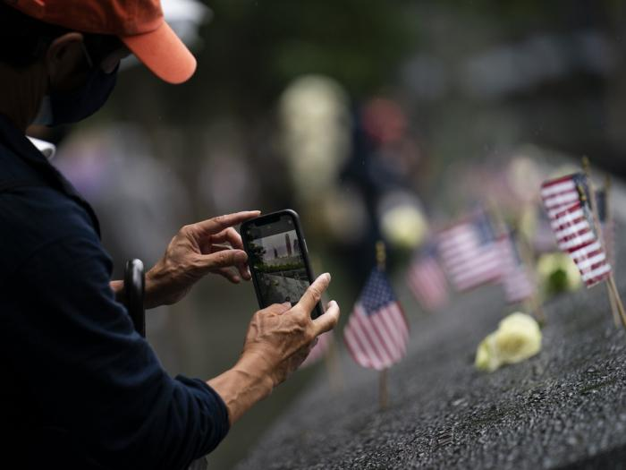 A visitor takes a photograph of flowers and American flags resting among the names of those who died at the National September 11 Memorial & Museum, Thursday, Sept. 9, 2021, in New York